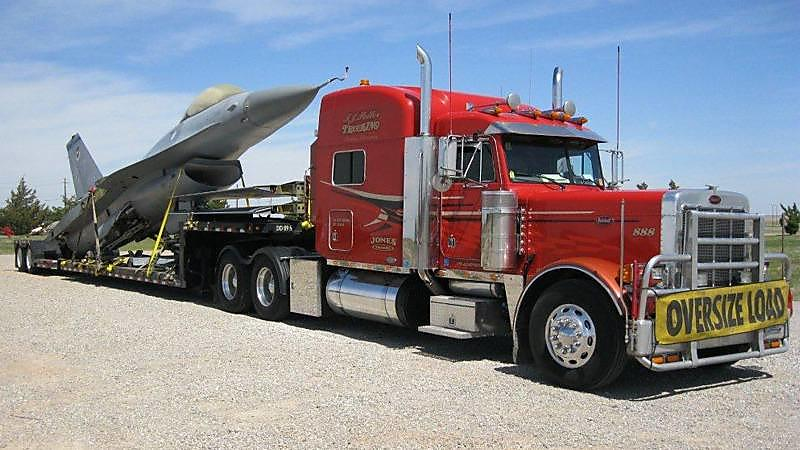 Flatbed Truck Driving Transporting A Fighter Jet on the Road