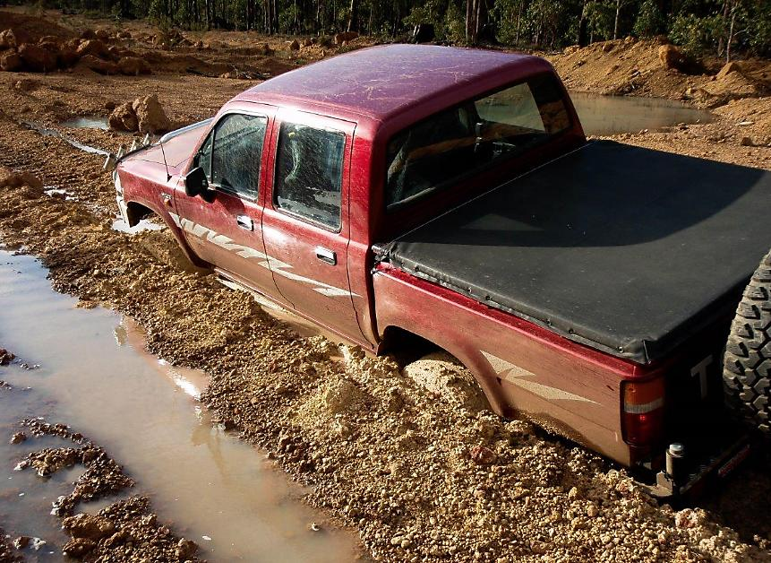 Truck stuck in the mud using a ratchet strap to recover