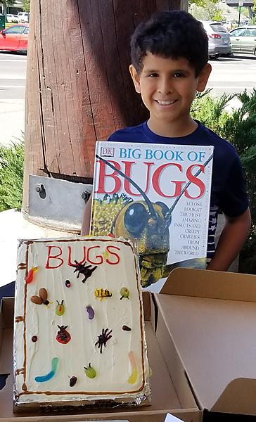 Boy with book about bugs and cake with bugs
