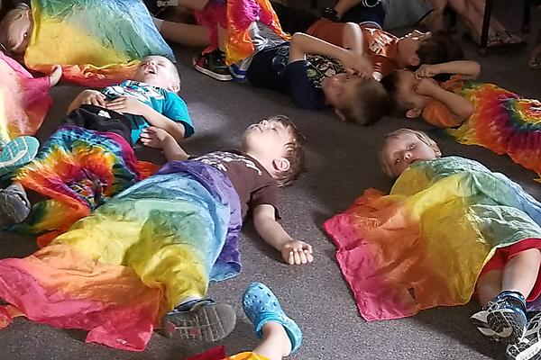 children under tiedye scarves at music school program