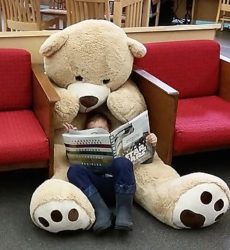 Big teddy bear reading a book