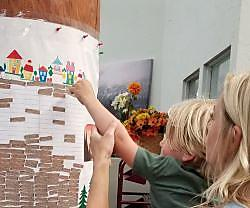 Mom 38 toddler attach sticker to mural