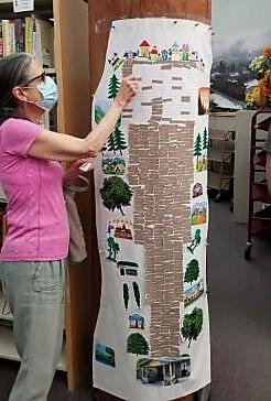 Adult reader attaching sticker to mural