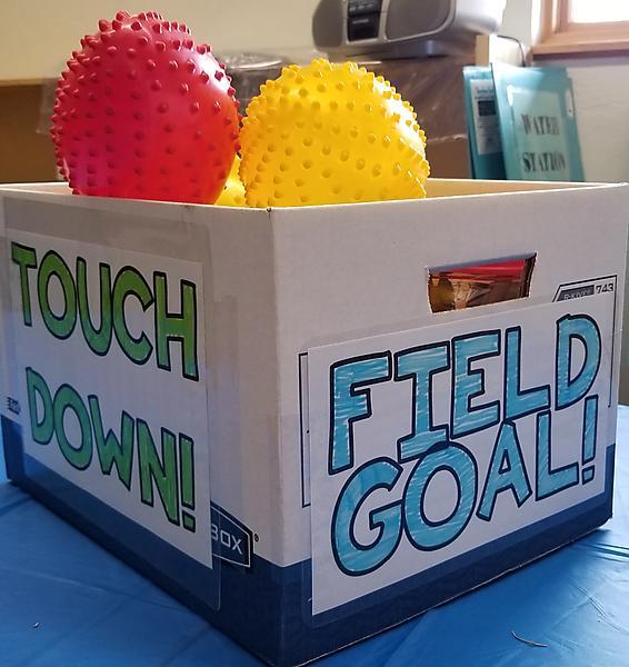 Colorful footballs inside cardboard box