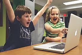 Excited boy and girl by laptop